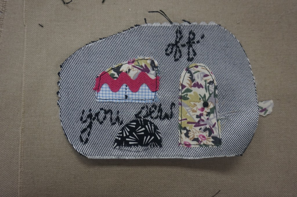 """Ater adding the curtain to the window, place and embroider all pieces on to the side panels. I added a french knot to the door for a handle, and the window for a drawstring. I also embroidered """"Off you sew"""" to the caravan's side. HINT: Use the pattern to help with placement of pieces."""