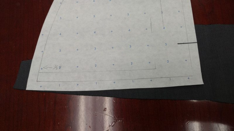 The pattern piece laid over a scrap left over from cutting the front and back pieces.