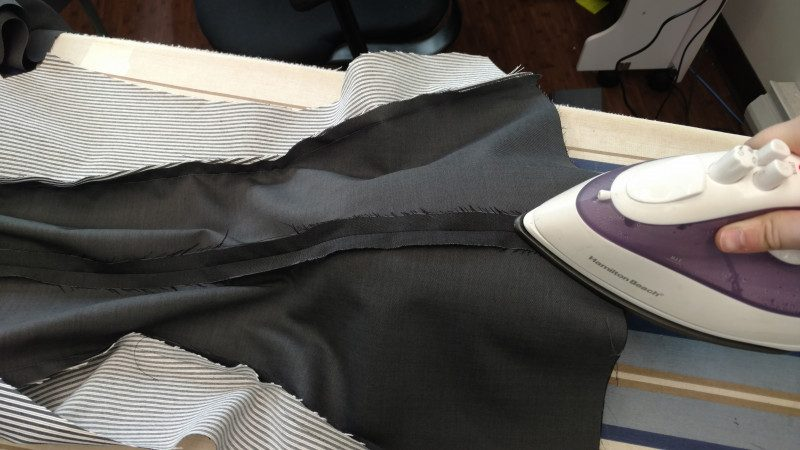 The tailor's ham supports the curve of the blazer while it is pressed.