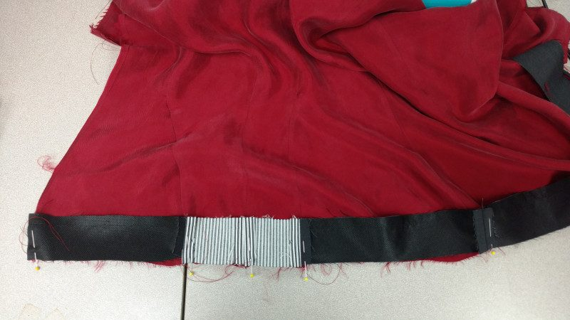 The shorter side of the hem facing gets attached to the lining. The lining will need to be gathered slightly to fit.