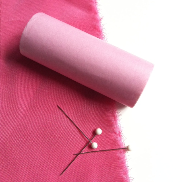 Pins and paper help stabilize silk when stitching. We show a roll of Mood's pink cash register tape here to use for easy paper strips.
